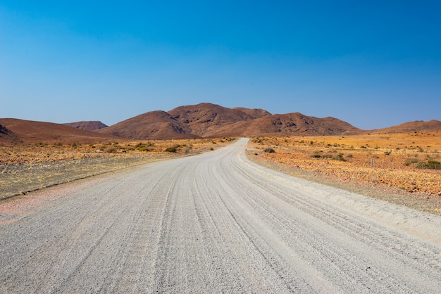 Route de gravier traversant le désert coloré de twyfelfontein, dans le damaraland brandberg