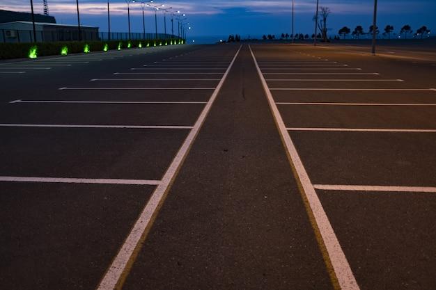 Route grise avec des lignes blanches et des panneaux contre le ciel bleu