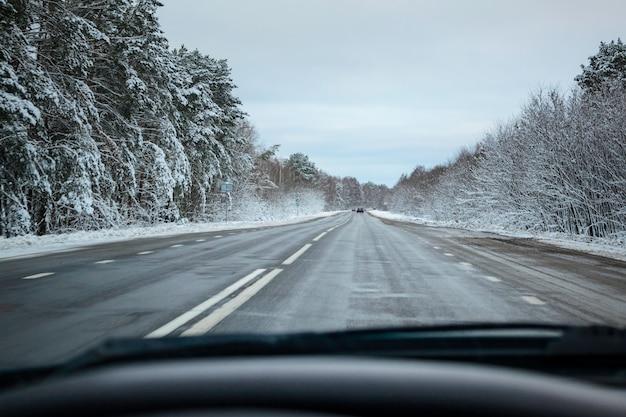 Route d'hiver enneigée depuis la fenêtre de la voiture.