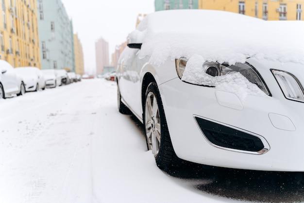 Route d'hiver le matin. vue en contre-plongée des voitures garées couvertes de neige dans la rue. notion de tempête de neige. stock photo