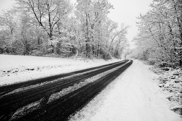 Route d'hiver avec de la neige au sol. voyagez de manière difficile pour profiter de la saison froide. image blanche avec de l'asphalte noir en contraste. concept de conduite et de voyage