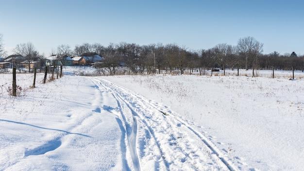 Route le long des champs enneigés jusqu'au village, heure d'hiver