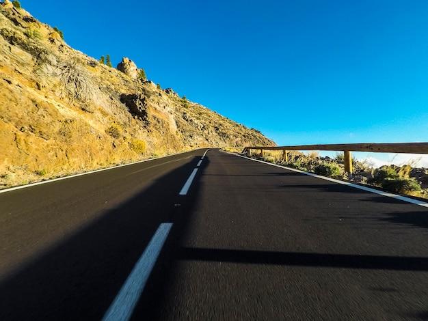 Route longue à la montagne avec monture vulcaine à l'avant et ciel bleu clair - point de vue au sol avec asphalte noir et lignes blanches - concept de conduite et de voyage