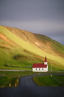 Route menant à l'église. reyniskirkja - église islandaise typique près de la plage de reynisfjara, islande