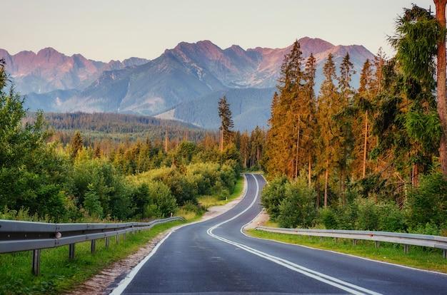 La route mène à travers les bois aux montagnes