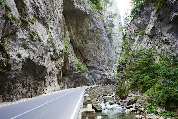 Route de montagne dans de hautes falaises rocheuses verticales