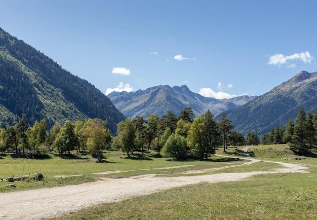Route de montagne dans un panorama d'une vallée de montagne ensoleillée
