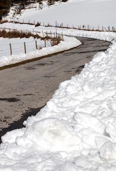 Route de montagne avec de la neige accumulée sur les côtés par le chasse-neige