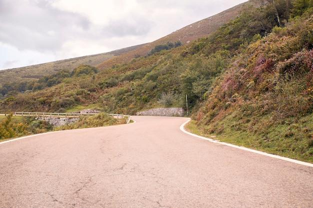 Route de montagne sinueuse entre les champs verts sous les nuages d'automne
