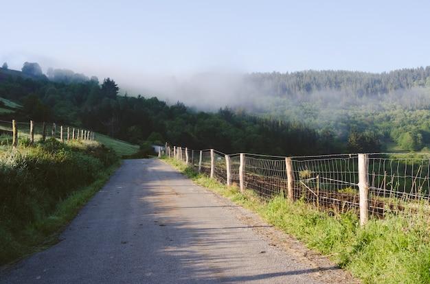 Route avec montagnes en arrière-plan avec brouillard.