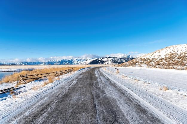 Route avec de la neige et du froid dans le parc national de grand teton, wyoming