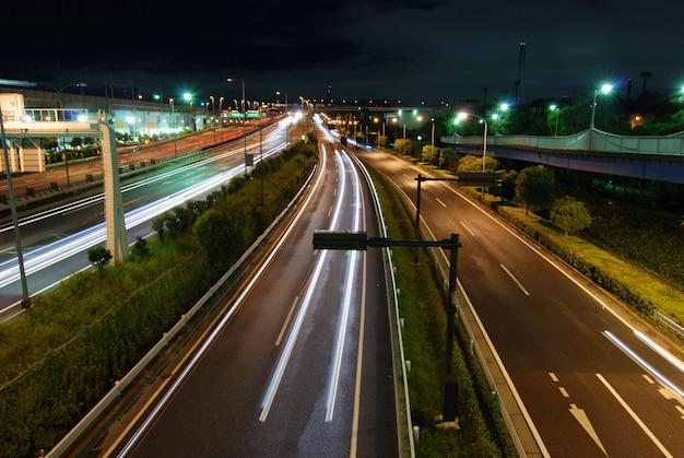 Route de nuit droite avec traces de voiture