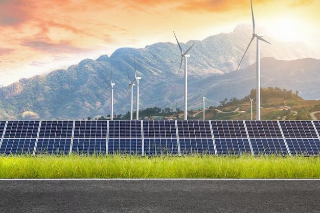 Route avec des panneaux solaires avec des éoliennes contre le paysage de mountanis contre le ciel coucher de soleil