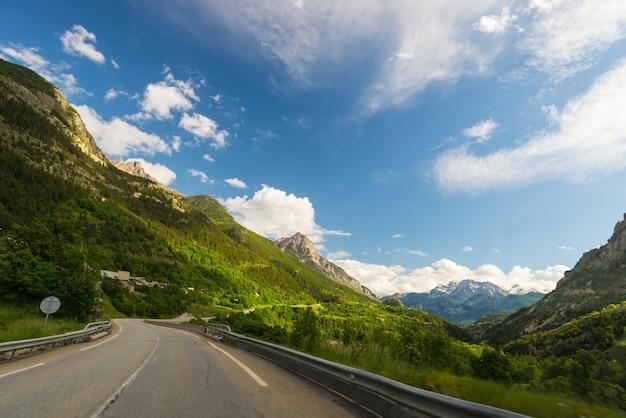 Route pavée à deux voies dans un paysage alpin pittoresque et un ciel maussade. vue panoramique de la caméra montée en voiture.