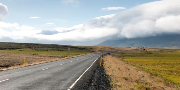 Route pavée disparaissant à l'horizon vers des montagnes couvertes de mottes
