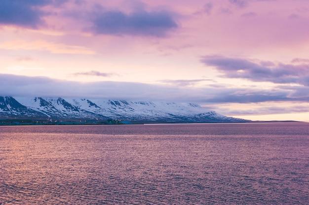 Route de paysage de nature d'islande avec des nuages et un village de champ amplement et une rivière de lac