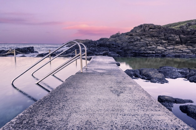 Route de pierre dans la formation de l'eau au bord de la mer pendant le coucher du soleil