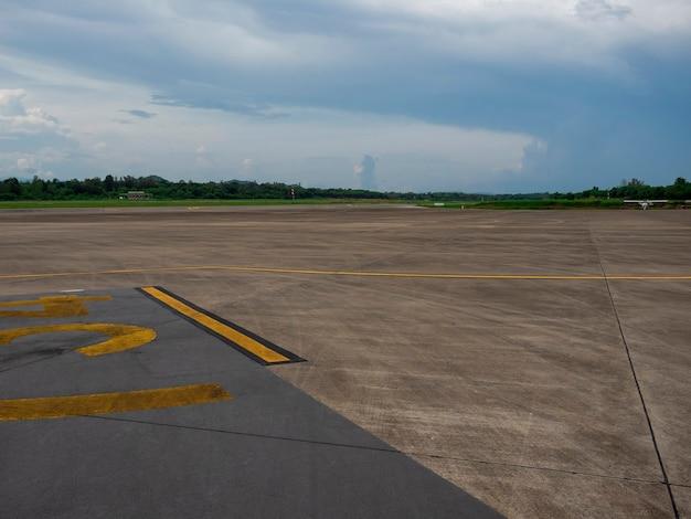 Route de piste de ciment vide dans l'aéroport de campagne avec ciel de nuages de pluie