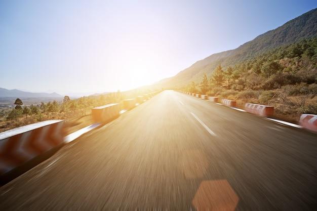 Route avec point de fuite au coucher du soleil