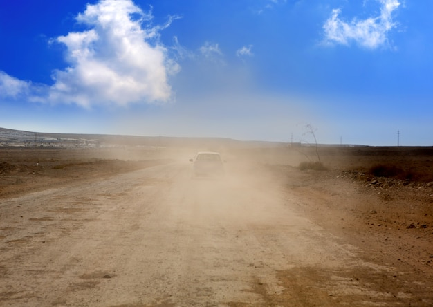 Route de poussière avec voiture dans le brouillard brun à lanzarote