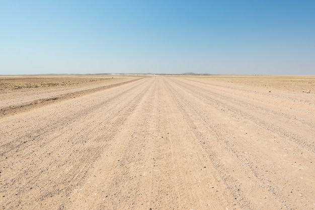 Route rectiligne en gravier traversant le désert coloré du namib, dans le majestueux parc national de namib naukluft, meilleure destination de voyage en namibie, afrique.