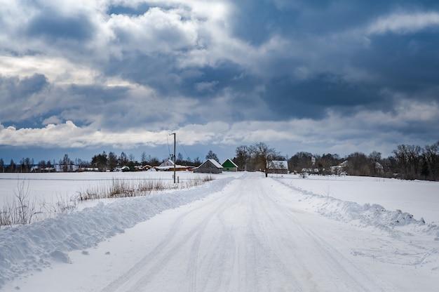 Route rurale menant à travers les champs jusqu'à la route enneigée avec un ciel dramatique en hiver