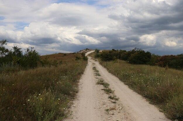 Route de sable vers les nuages route de sable blanc vers le ciel nuageux et herbe verte sur le côté