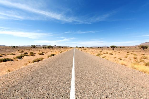 Route sans fin dans le désert du sahara avec ciel bleu, afrique