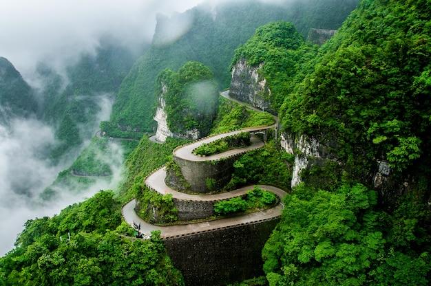 La route sinueuse du parc national de montagne de tianmen (zhangjiajie) dans la brume de nuages, chine