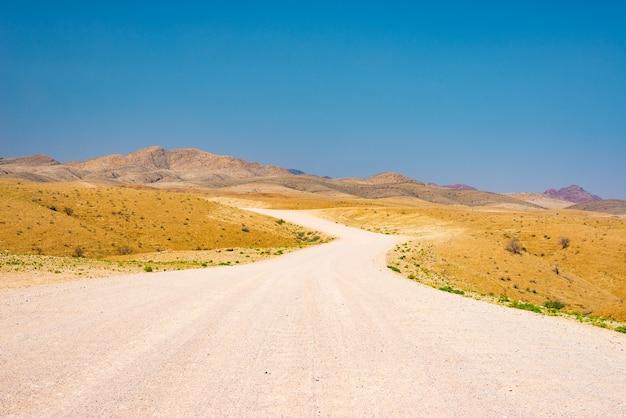 Route sinueuse en gravier traversant le désert coloré du namib, dans le majestueux parc national de namib naukluft, meilleure destination de voyage en namibie, afrique.
