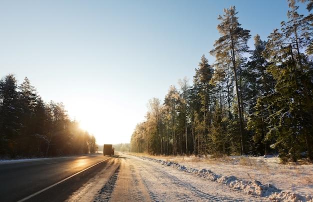 Route à travers la forêt d'hiver