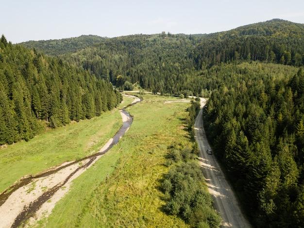 Route à travers les montagnes et la forêt capturée d'en haut