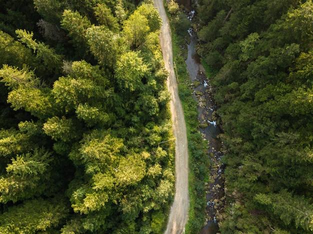 Route à travers montagnes et forêts capturées d'en haut