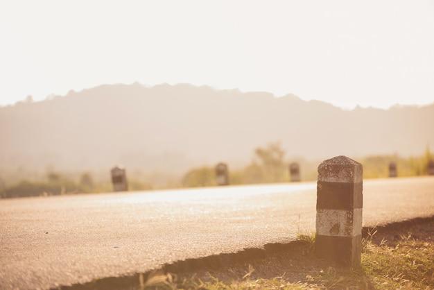 Route à travers le paysage. route et voiture panoramiques et coucher de soleil. concept de voyage de route.