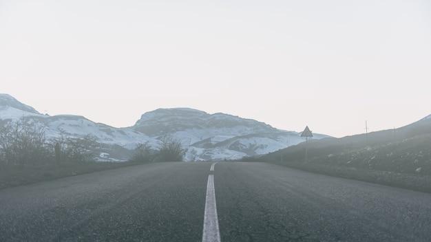 Route vers les montagnes enneigées brumeuses