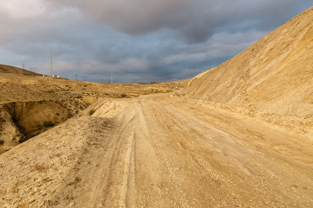 Route vers les volcans de boue de gobustan près de bakou, azerbaïdjan. route et ciel orageux