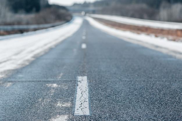 Route vide d'hiver avec une ligne blanche en pointillés dans la journée