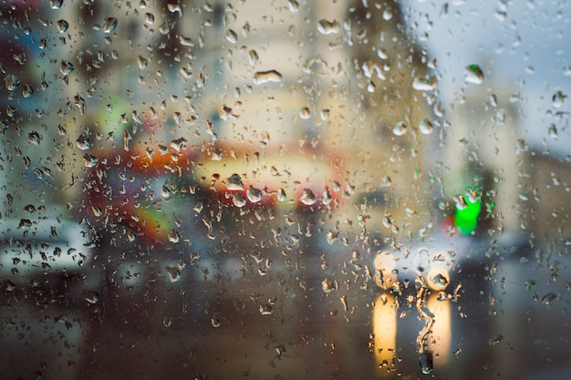 Route de la ville vue à travers les gouttes de pluie sur le pare-brise de la voiture