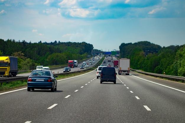 Route avec des voitures et ciel bleu avec des nuages.