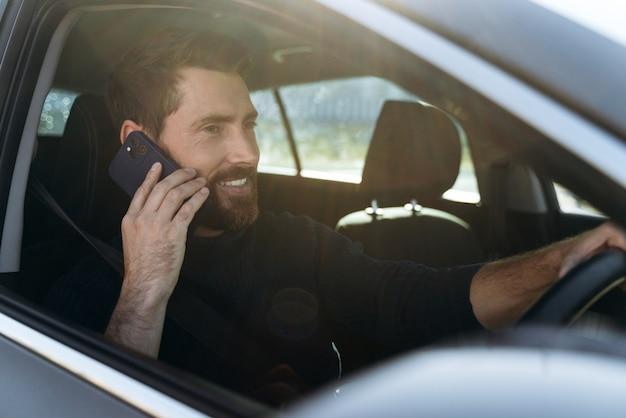 A la route. vue portrait de l'homme caucasien attentif regardant la fenêtre tout en discutant via smartphone avec son collègue pendant le long chemin vers le travail
