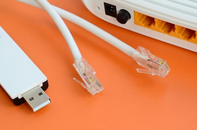 Routeur internet, adaptateur usb portable wi-fi et fiches de câble internet se trouvent sur un fond orange vif.