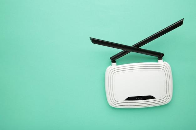 Routeur wi-fi blanc avec antennes noires sur surface menthe avec espace de copie