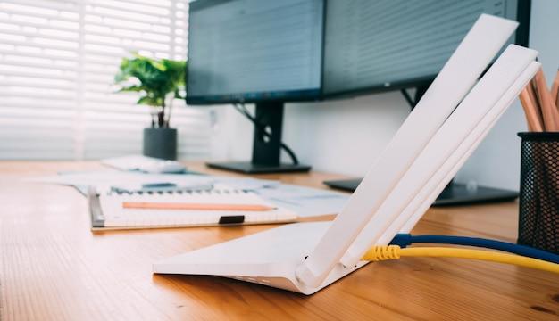 Routeur wi-fi moderne sur table lumineuse au bureau à domicile