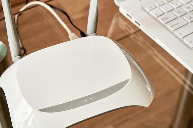 Routeur wi-fi sans fil blanc près d'un ordinateur portable sur une table en verre