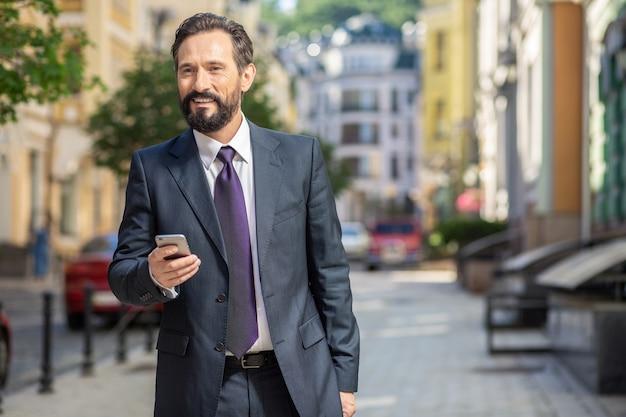 Routine des affaires. enthousiaste homme d'affaires adulte va travailler en se tenant debout dans la rue