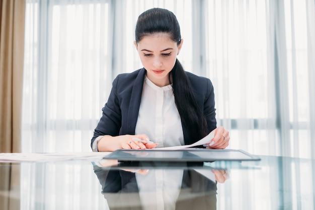 Routine de bureau. femme travaillant avec des papiers assis à son bureau