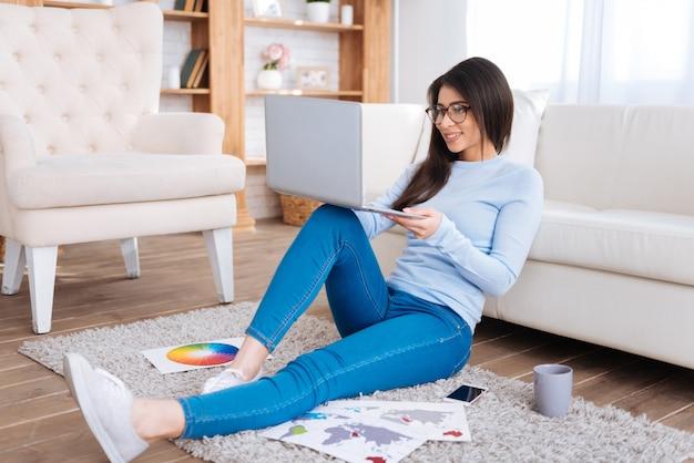 Routine des étudiants. charmante étudiante agréable assis sur le sol tout en travaillant sur un ordinateur portable