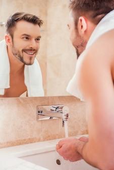Routine matinale. beau jeune homme se lavant les mains dans la salle de bain en se tenant debout devant le miroir