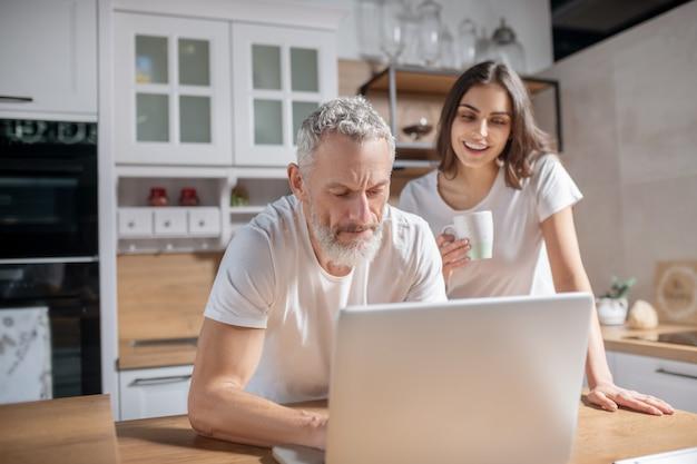 Routine matinale. un couple vérifiant les e-mails du matin tout en prenant un café