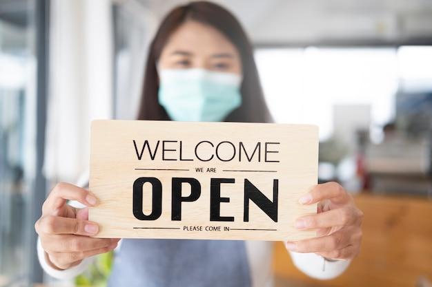Rouvrir, jeune fille asiatique porter un masque facial tournant un signe de fermé à ouvert après le verrouillage.